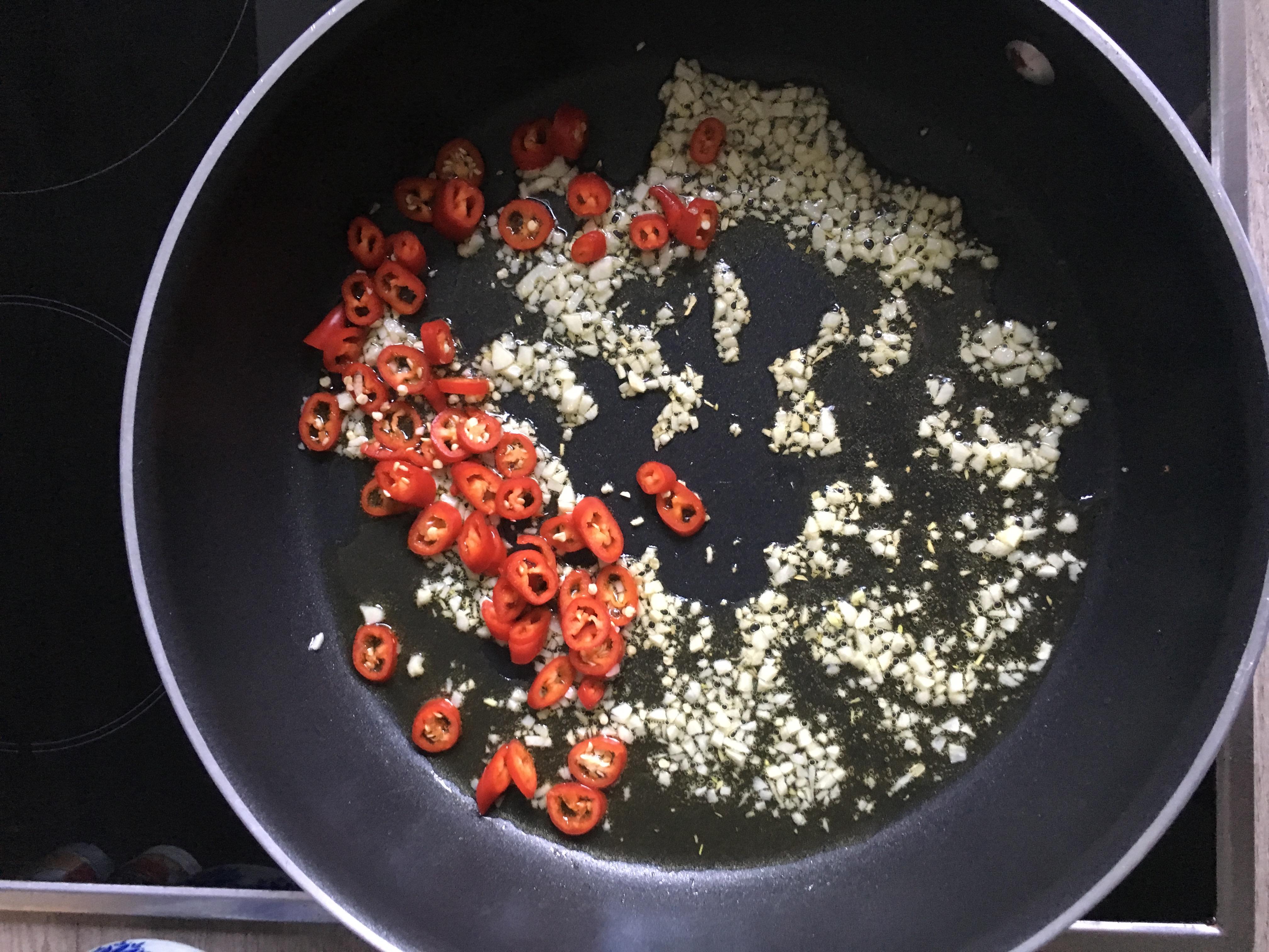 Knoblauch und Peperoni beim anbraten